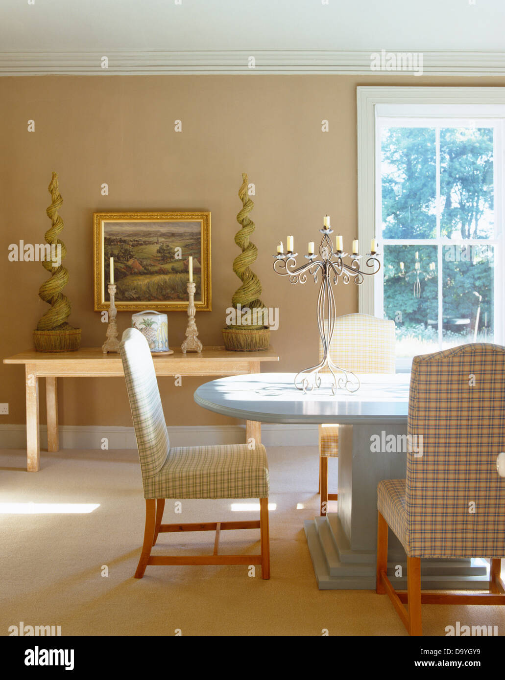 Checked upholstered chairs at modern oval table in beige country dining room with faux topiary on console table Stock Photo