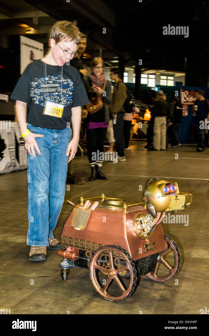 Boy is enthralled by robotic dog at the Vancouver Mini Maker Faire. - Stock Image