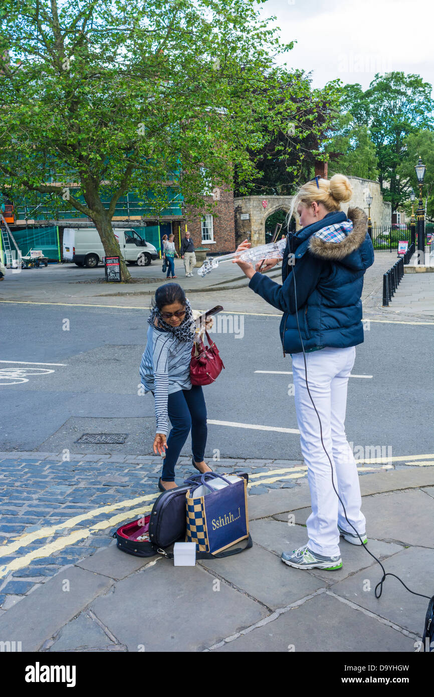 Tourist making donation to busker, York, England, June - Stock Image