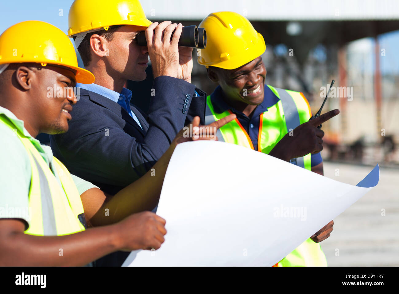 project manager using binoculars looking at the construction site with workers - Stock Image