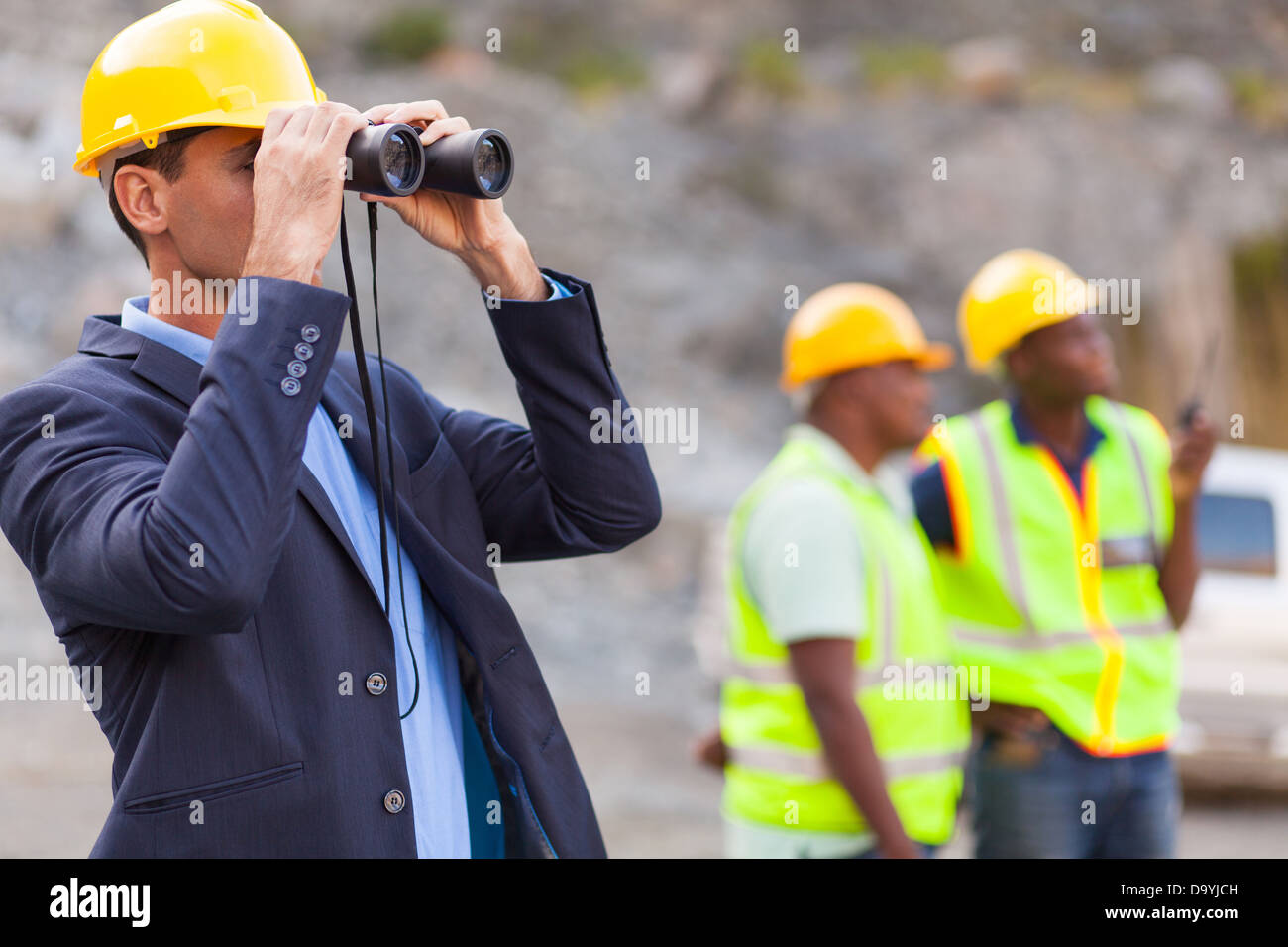 mine manager with binoculars at mining site - Stock Image