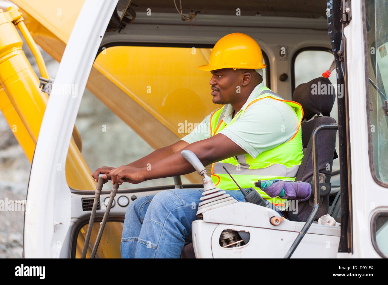 African American man operates excavator on building site - Stock Image