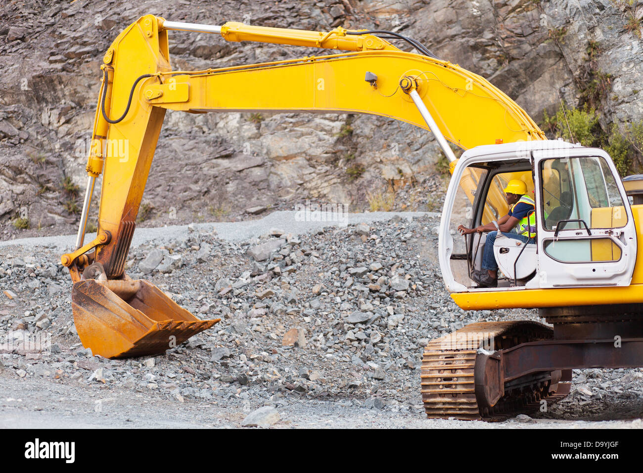 African road construction worker operating excavator on construction site - Stock Image