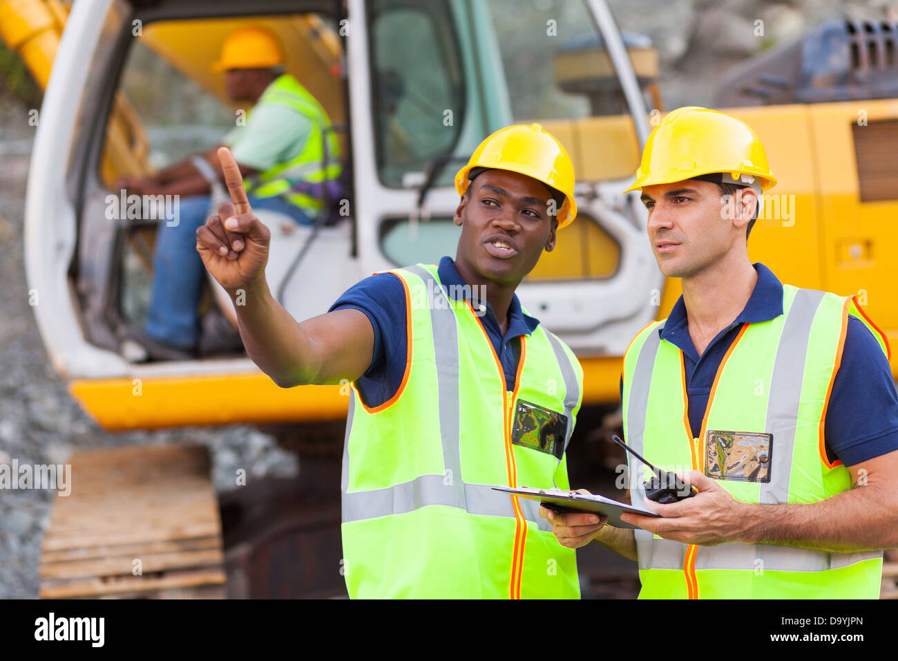 co-workers talking at construction site with bulldozer behind them - Stock Image