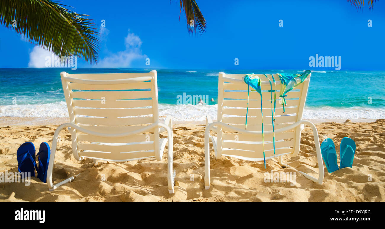 Ordinaire Two White Beach Chairs Under Palm Leaves By The Ocean, With Bikini And Flip  Flops And Couple In The Ocean On Background