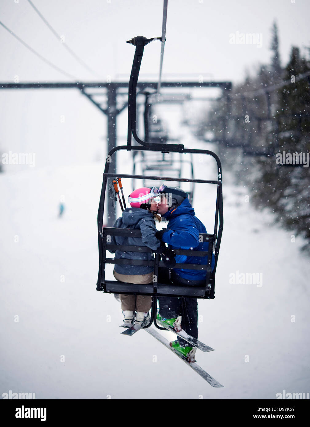 A couple share a kiss on a chairlift in softly falling snow. - Stock Image