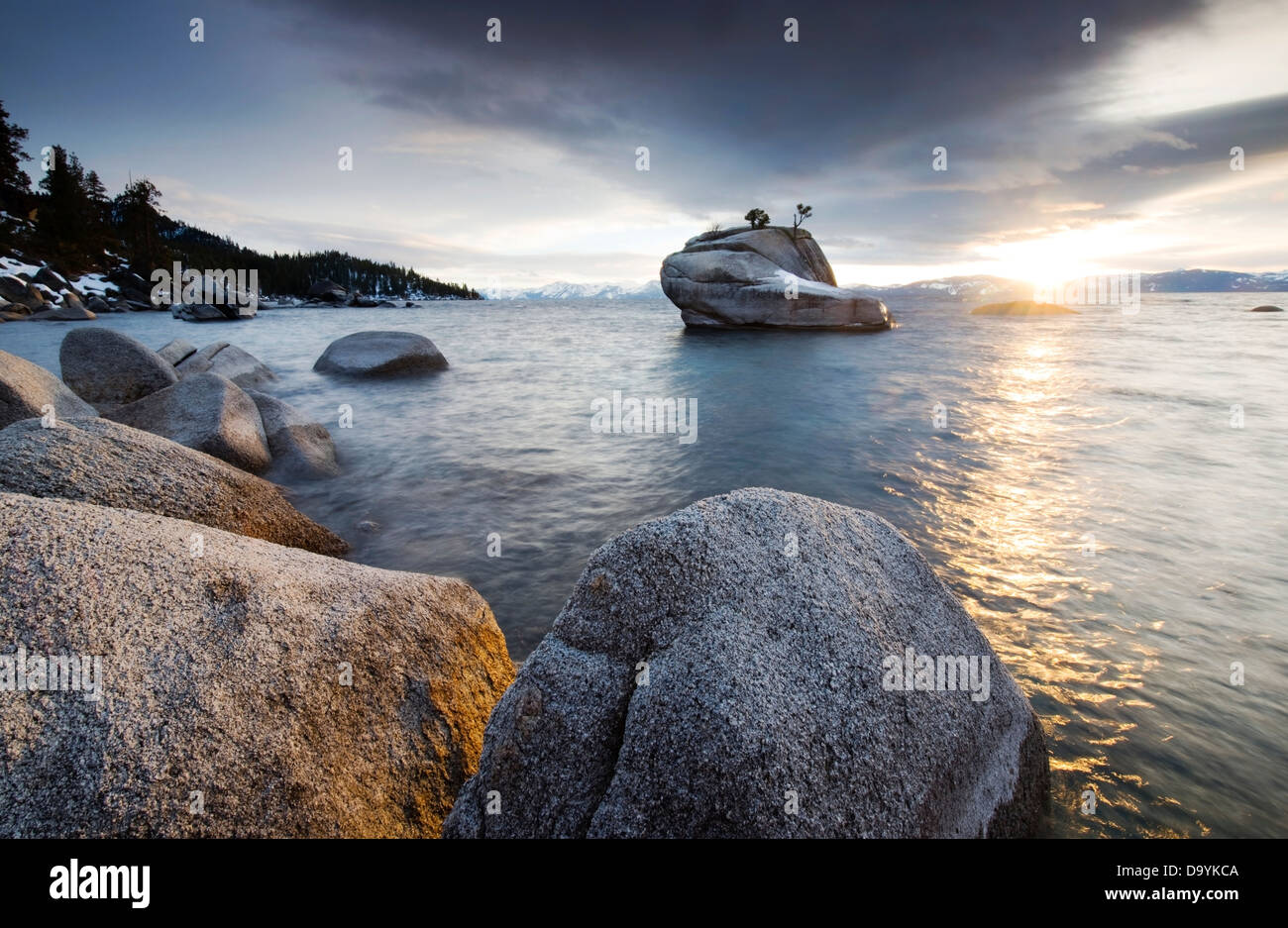 The sunset reflects off of Lake Tahoe and granite boulders on the east shore at a hidden location known as Bonsai - Stock Image