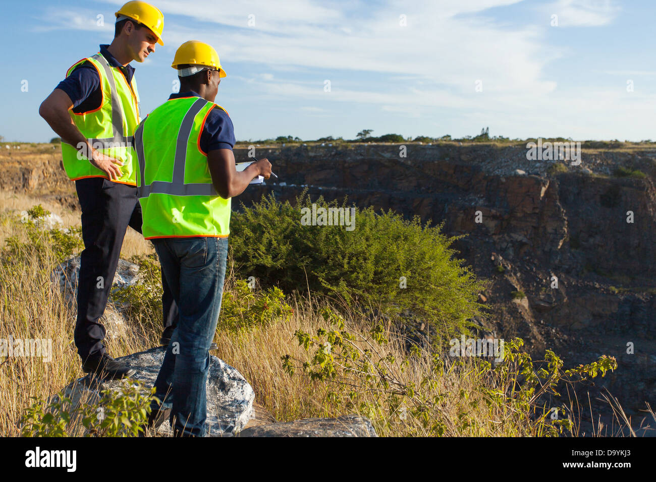 two male surveyors working at mining site - Stock Image