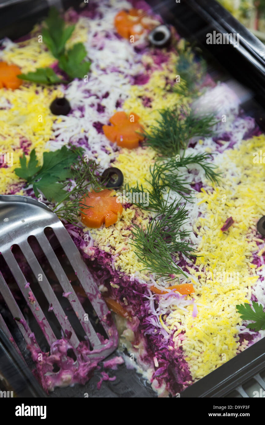 salad with herring for lunch in box shop-window - Stock Image