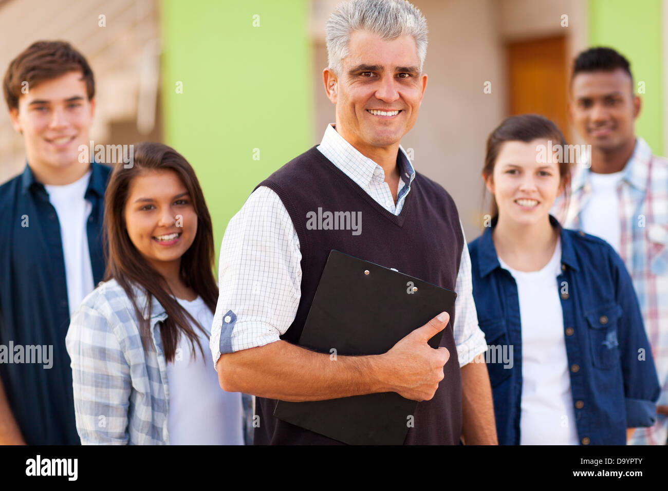 portrait of smiling high school teacher and students - Stock Image