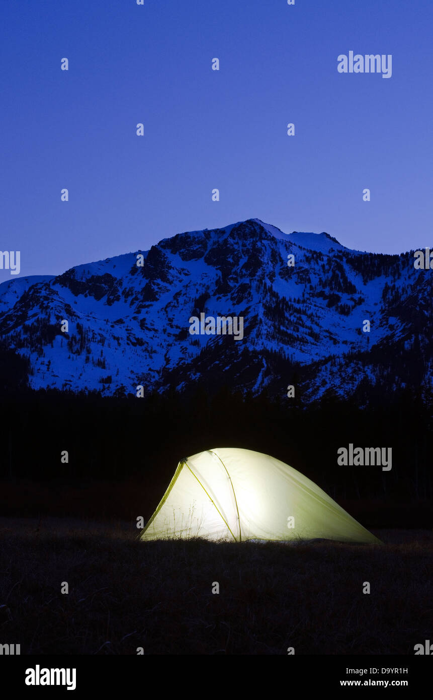 A tent is illuminated at dusk beneath Mount Tallac in Lake Tahoe, CA. - Stock Image