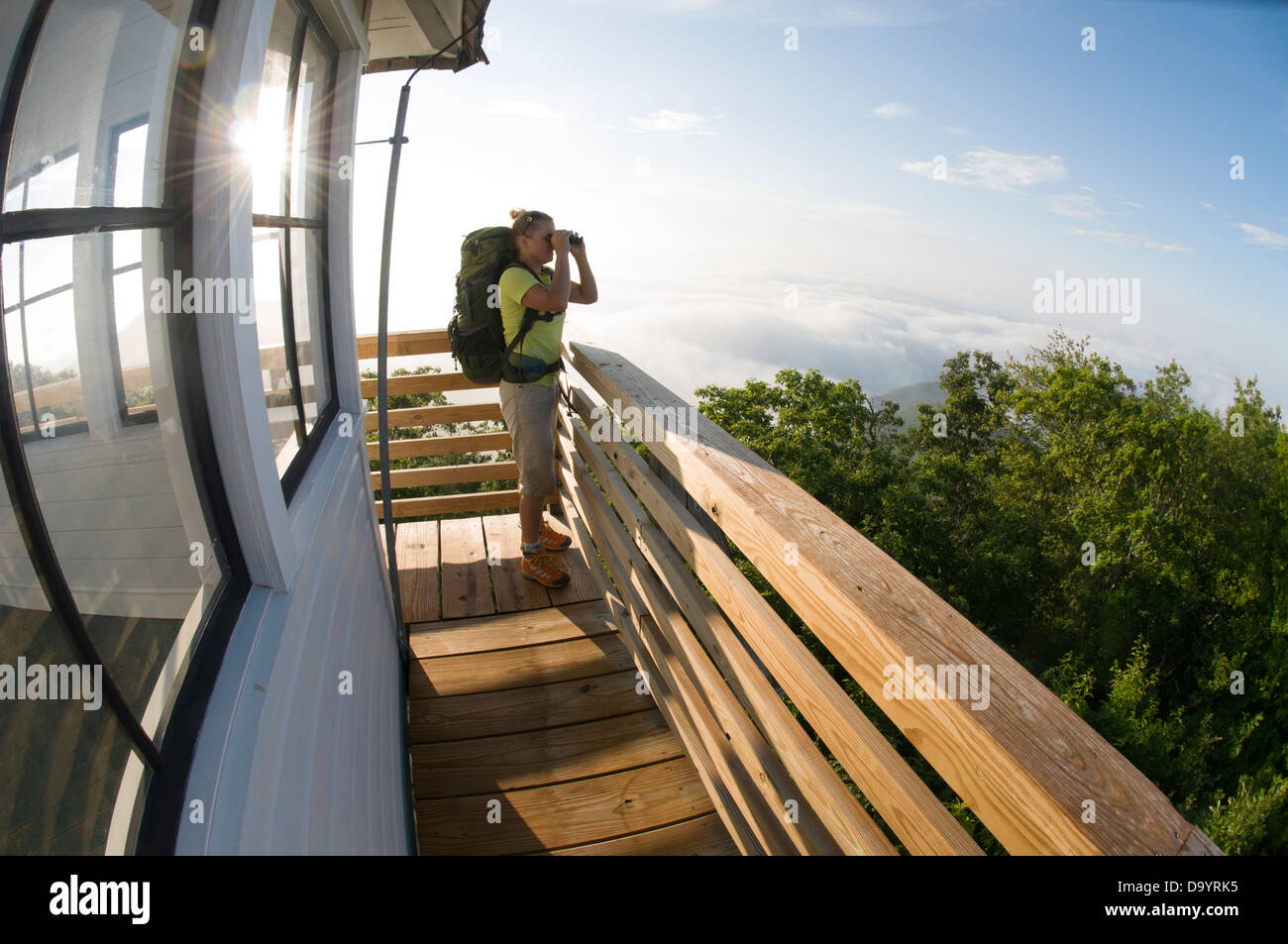 A woman backpacker looking through binoculars from the Green Knob Firetower, Pisgah National Forest, Asheville, - Stock Image