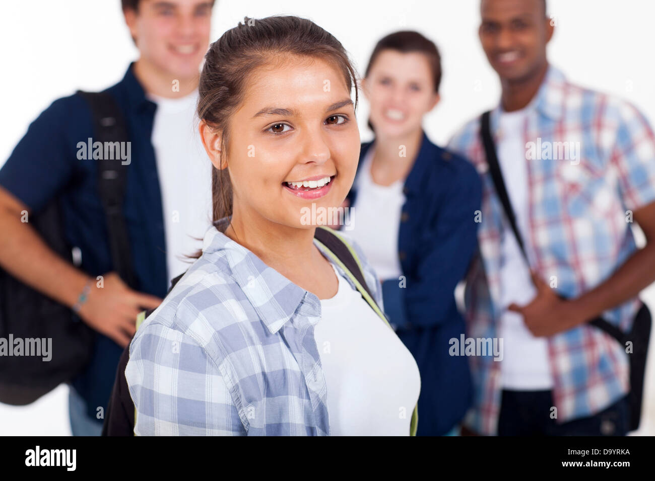 beautiful teenage girl with group of schoolmates over white background - Stock Image