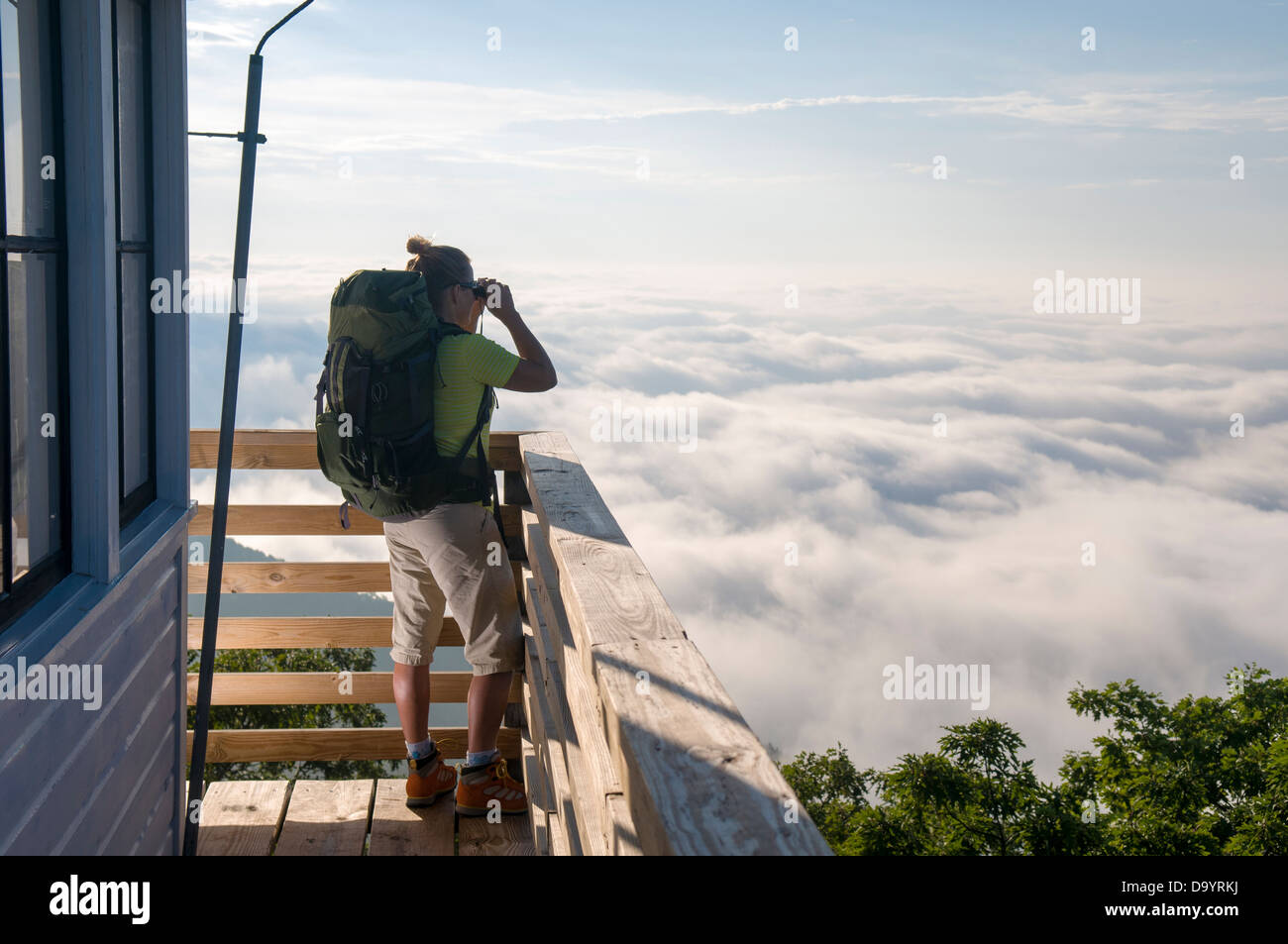 A woman backpacker looking through binoculars from the Green Knob Firetower, Pisgah National Forest, Asheville, Stock Photo