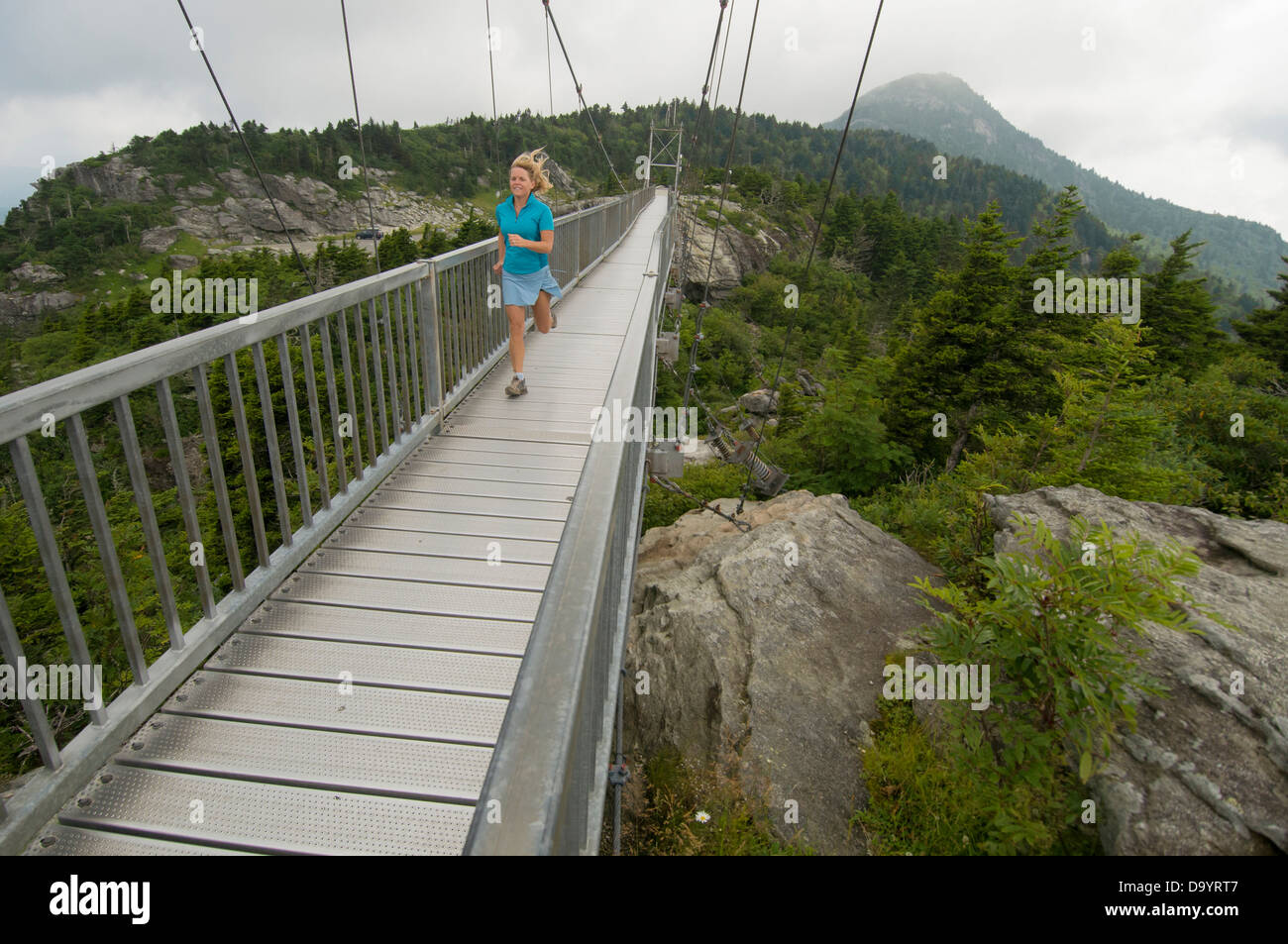 A Woman Running Across Suspension Bridge At Grandfather