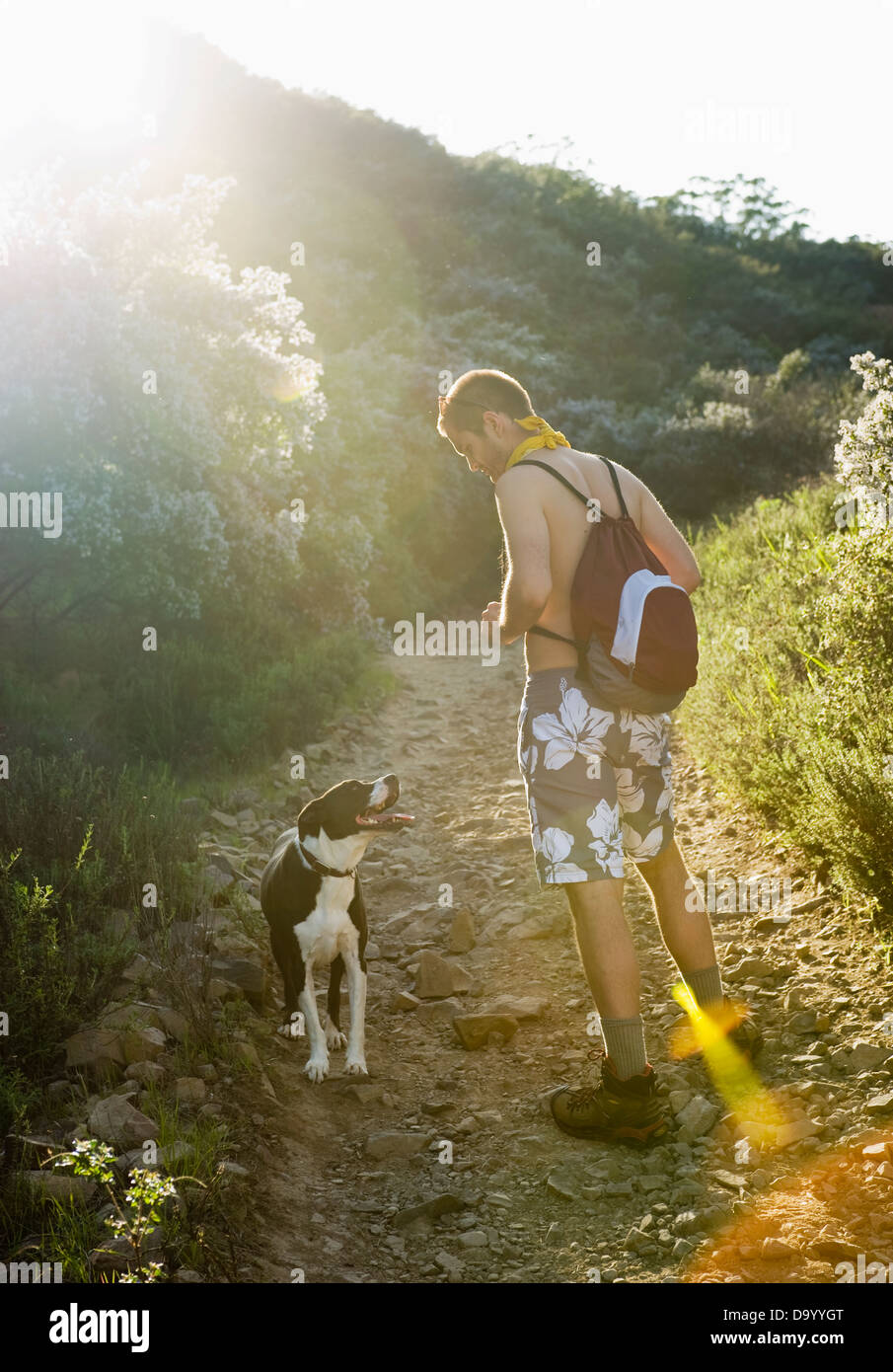 A hiker walks with his dog in the Santa Monica Mountains in California. - Stock Image
