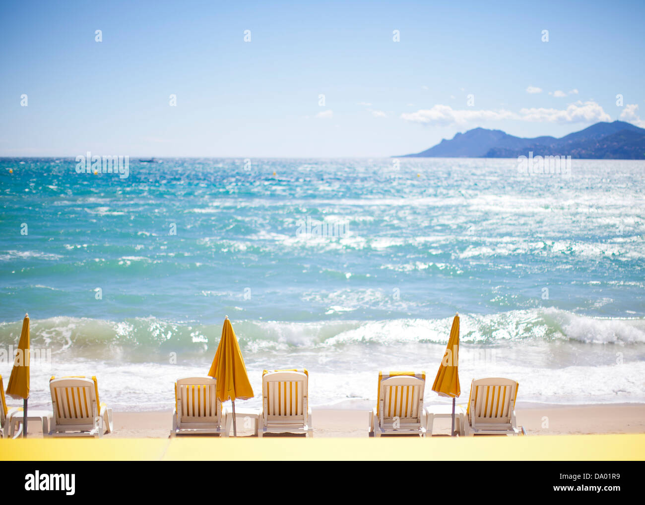 Row of yellow umbrellas and beach chairs on Mediterranean. - Stock Image