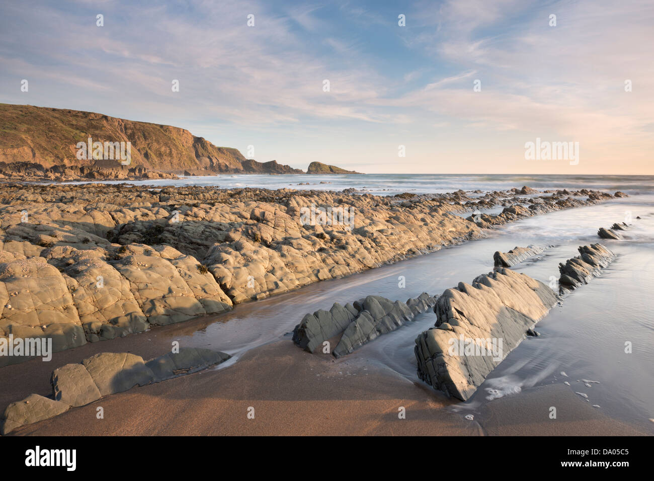 Evening light hits rocks on Welcombe Mouth Beach, North Devon, UK. Stock Photo