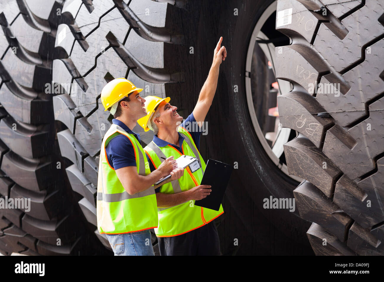 shipping company workers checking industrial tires before exporting - Stock Image