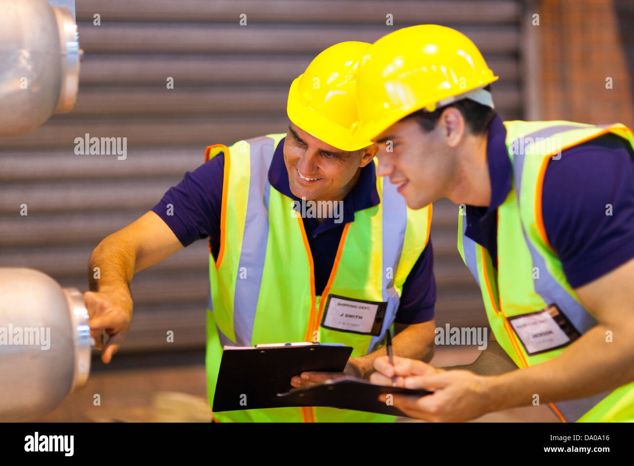 warehouse co-workers in safety gear inspecting machinery - Stock Image