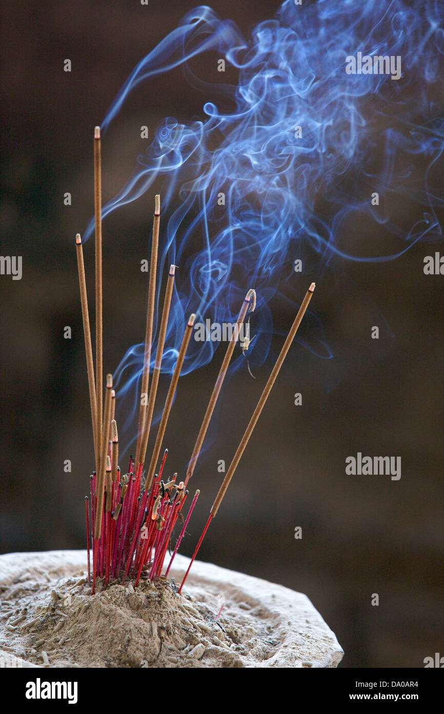 incense burns with blue curling smoke in a temple - Stock Image