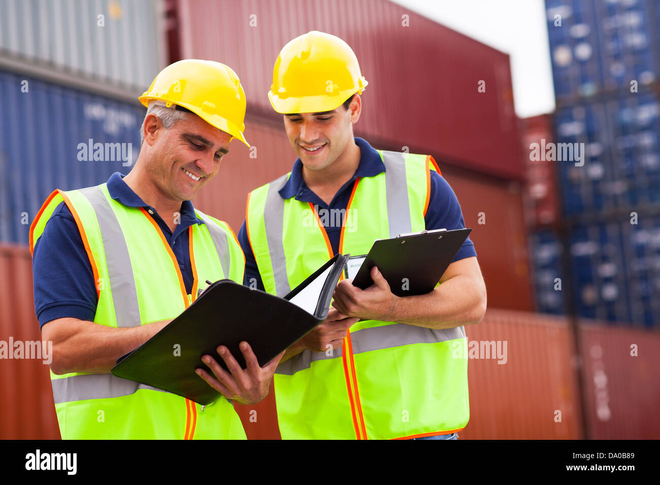 two harbor workers working at container yard - Stock Image