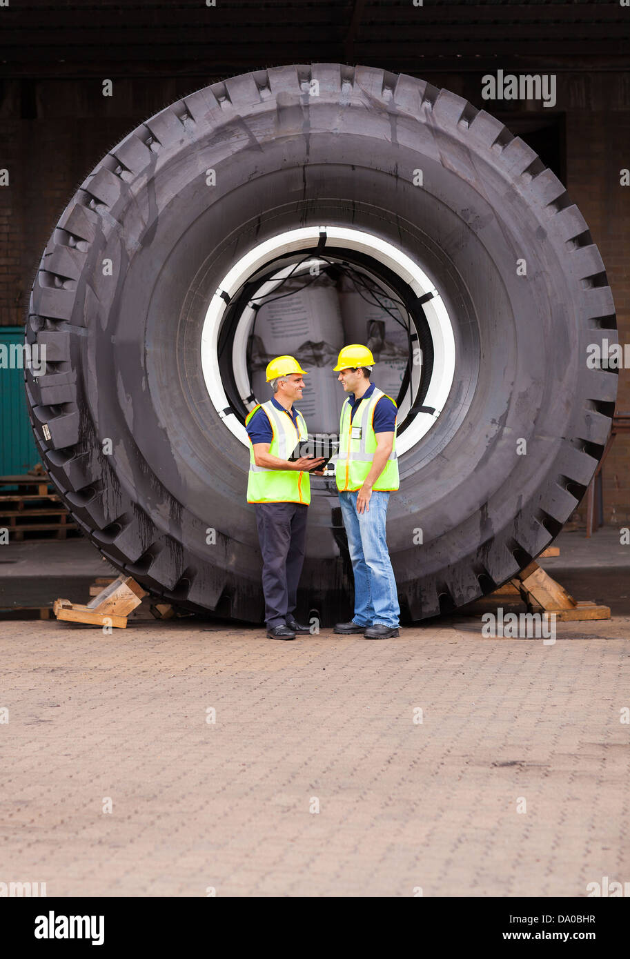cheerful warehouse workers standing in front of huge tire - Stock Image