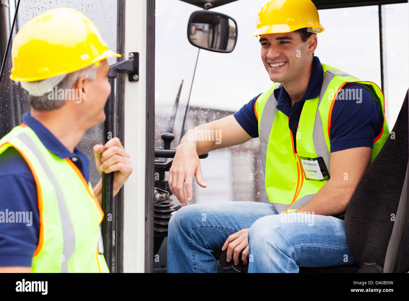 warehouse co-workers chatting during break on forklift - Stock Image