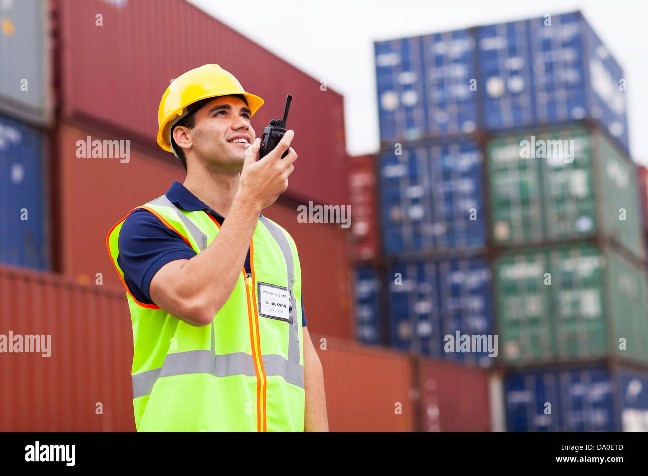 young harbor worker talking on the walkie-talkie at container warehouse - Stock Image