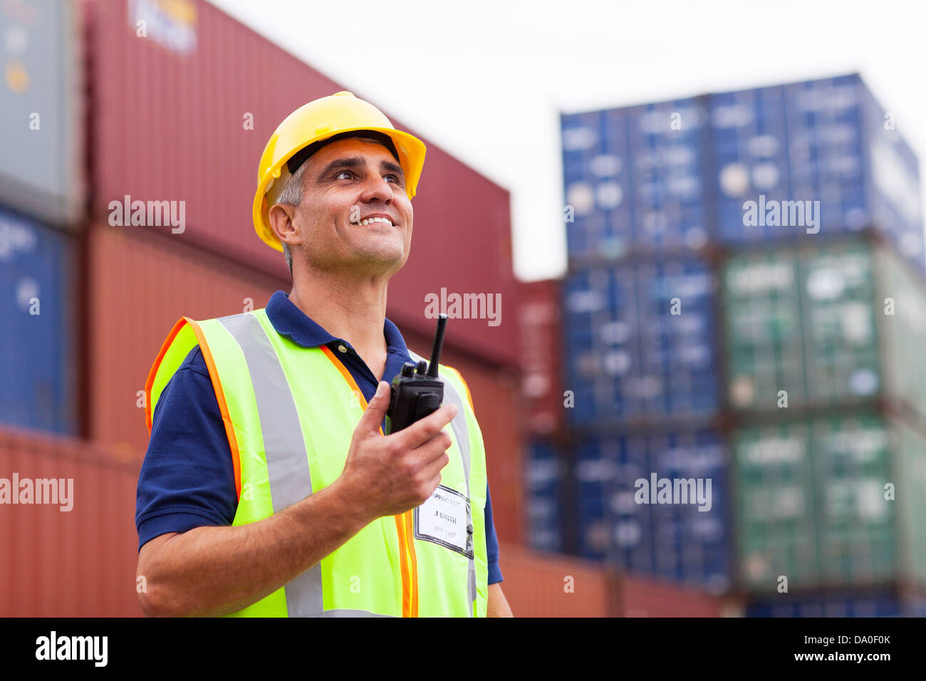 smiling middle aged warehouse worker holding radio at container yard - Stock Image