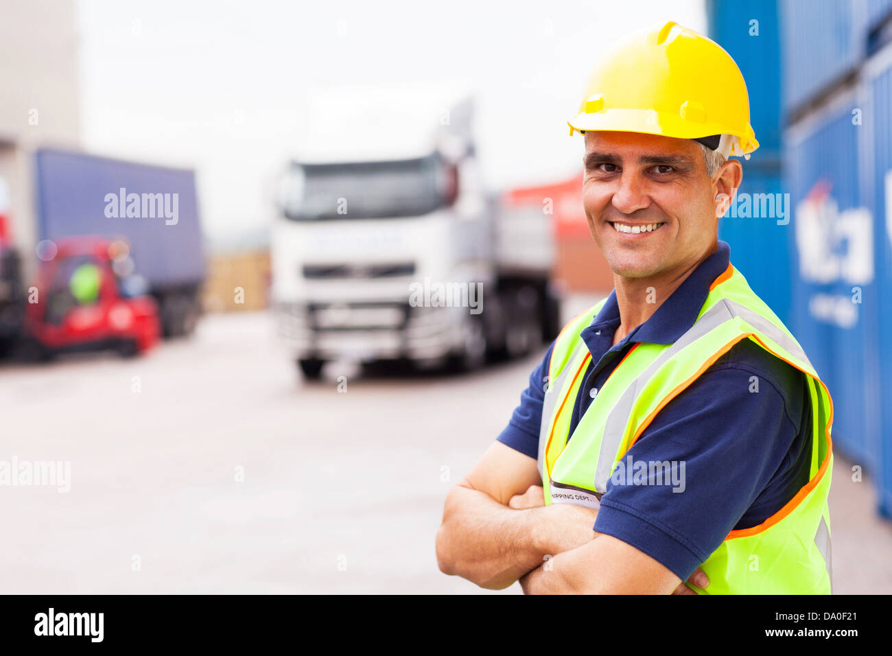 cheerful senior shipping company worker standing outside warehouse with arms crossed - Stock Image