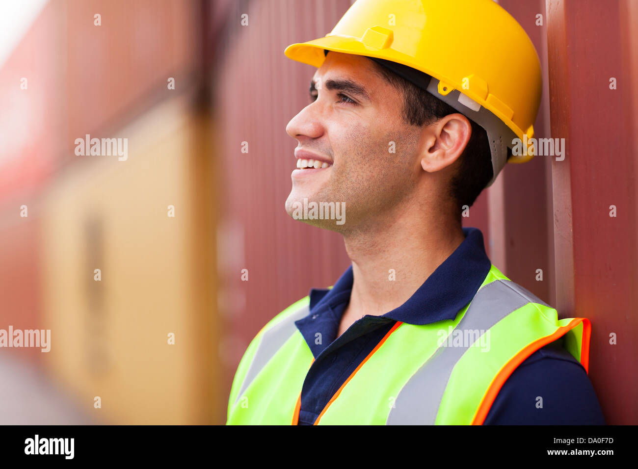 optimistic young harbor worker in container yard - Stock Image