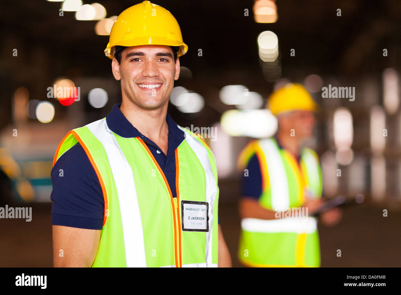 portrait of smiling young warehouse worker indoors - Stock Image