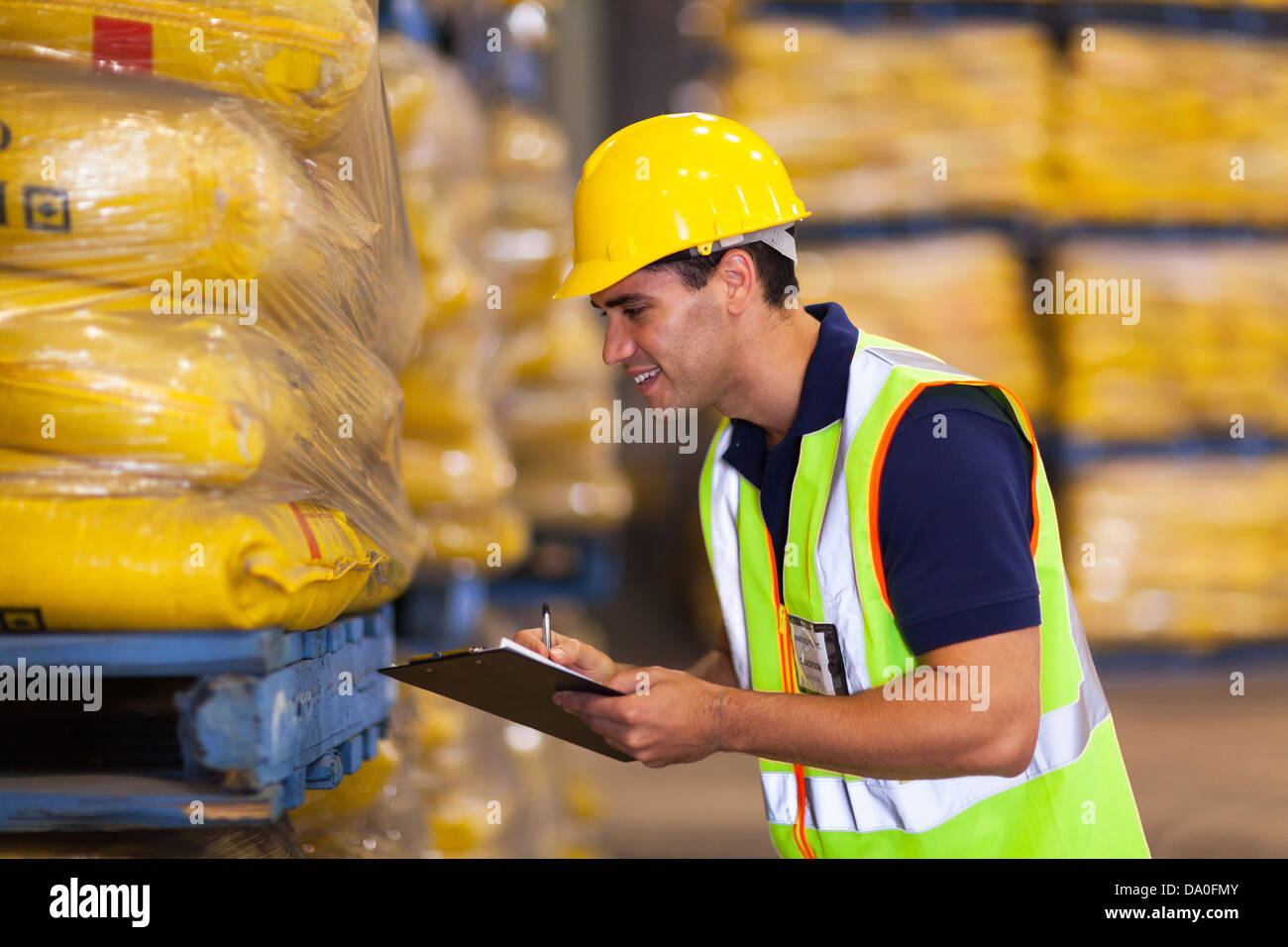 smiling young worker recording rice stock before delivery - Stock Image
