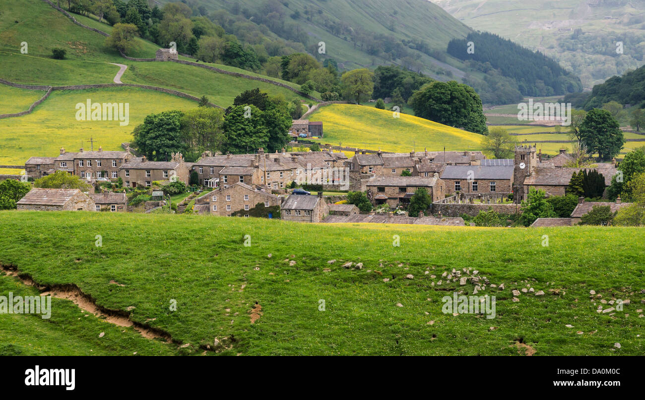The village of Muker, Swaledale, surrounded by traditional hay meadows. Kisdon Gorge shown behind the village. - Stock Image