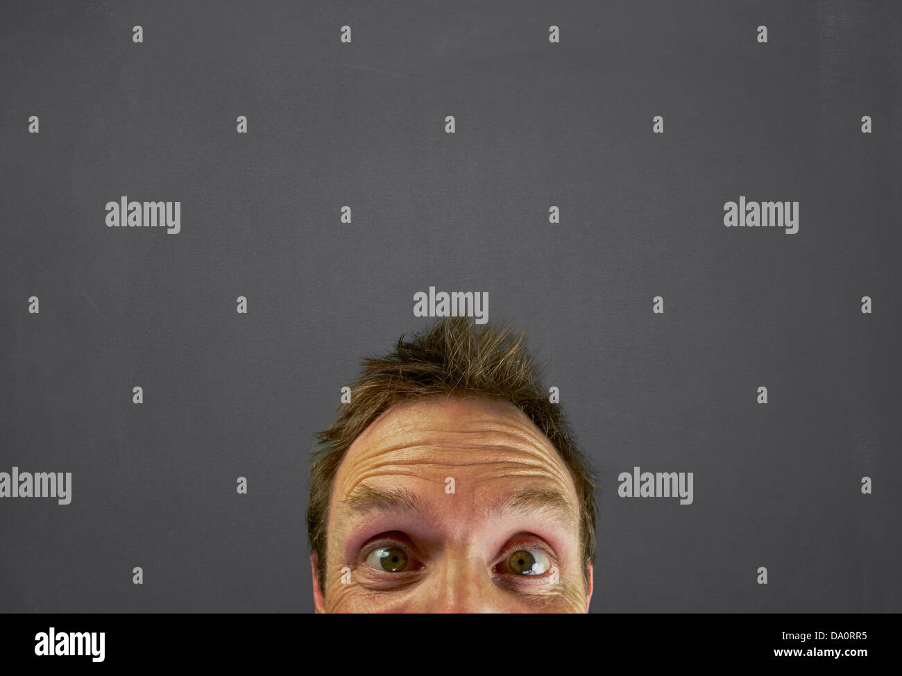 Mans Head in front of a chalkboard with a blankspace to write or draw a message above. - Stock Image