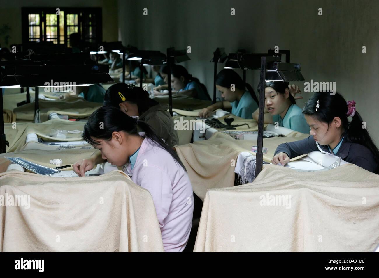 young women working at sewing factory making tedious handmade items, Hanoi, Vietnam Stock Photo