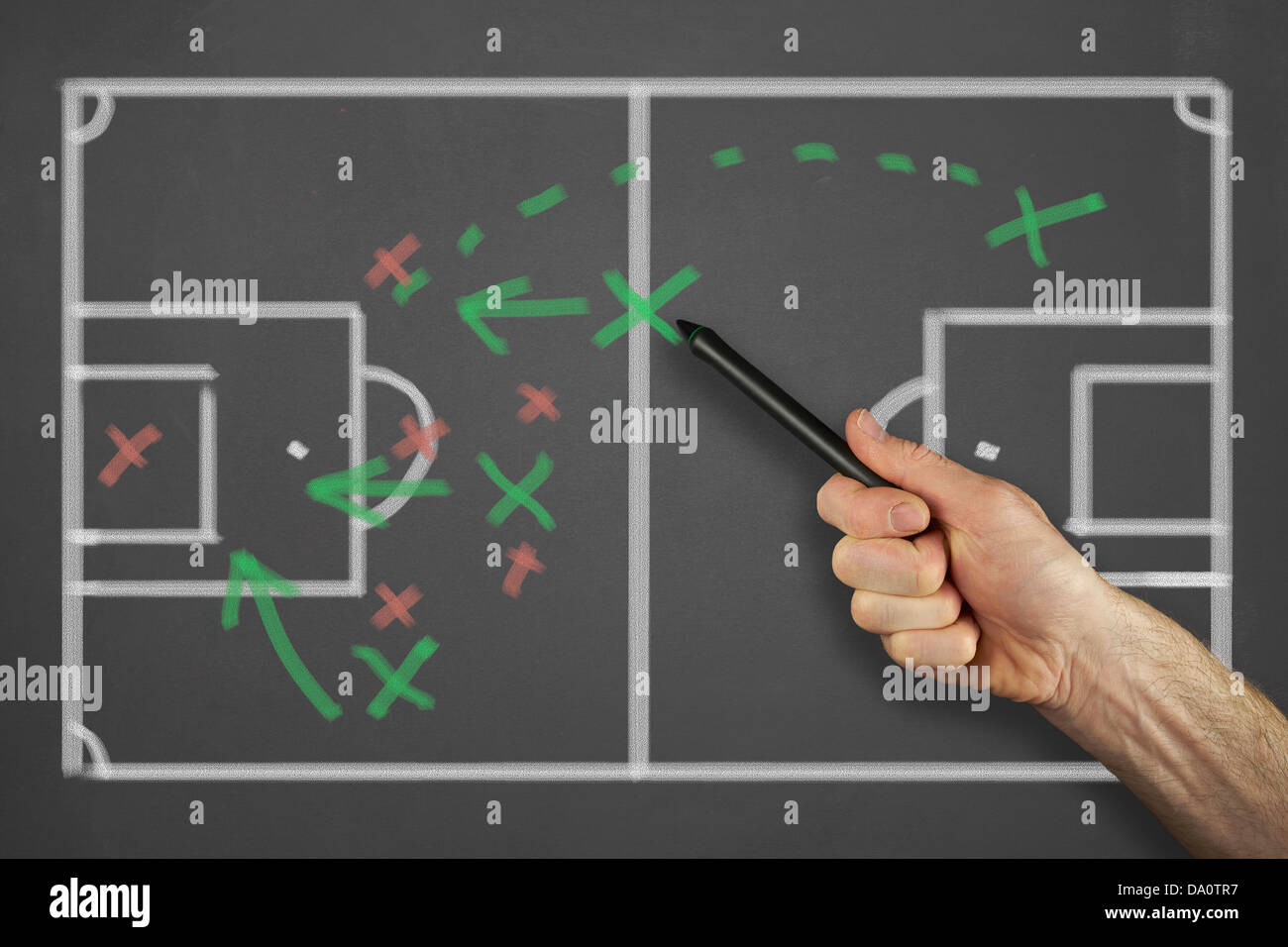 Mans hand pointing to a tactics message on a chalkboard. - Stock Image