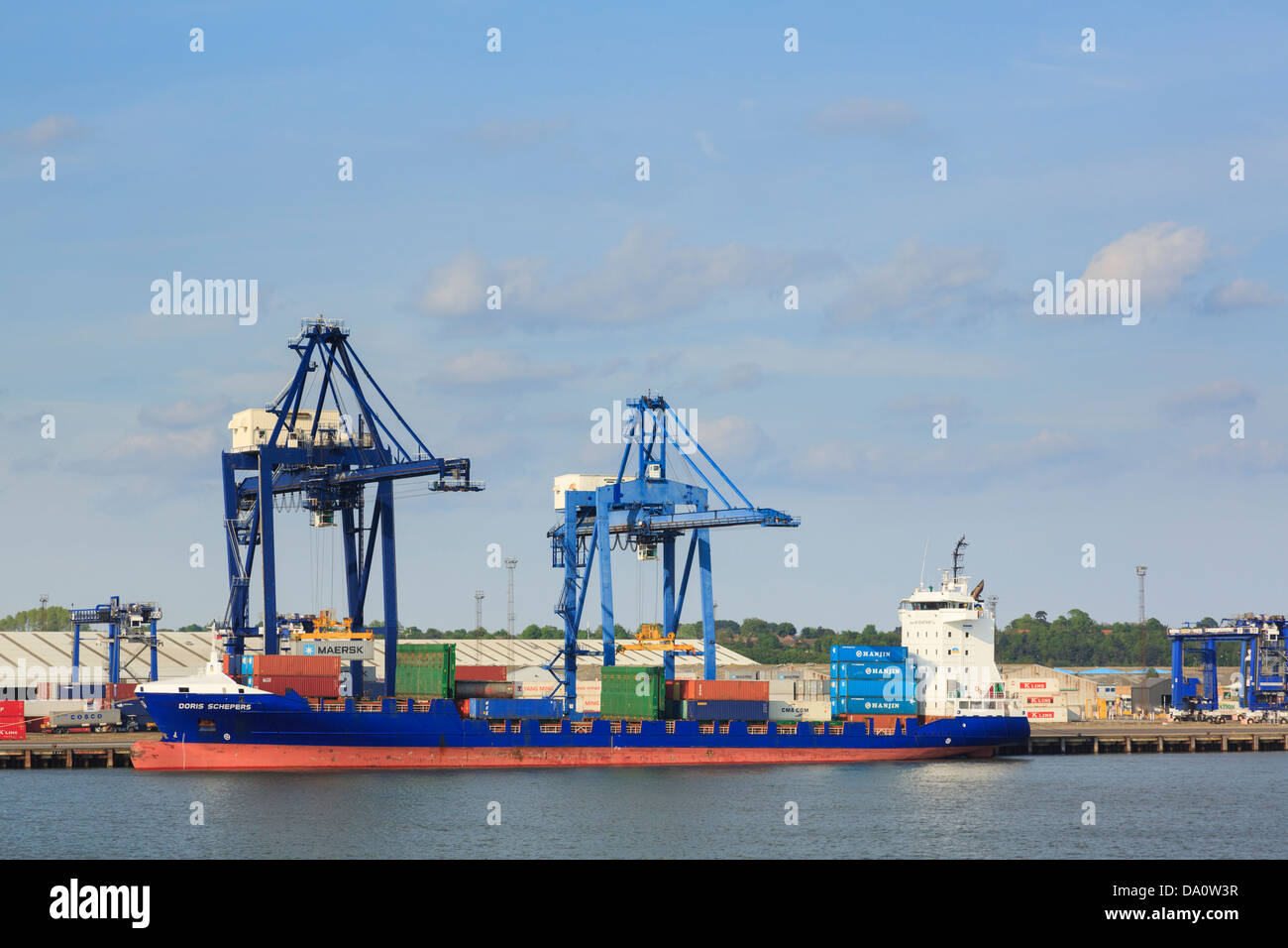Gantry crane lifting containers on to a container ship for global trade docked in terminal in Port of Felixstowe, Suffolk, England, UK, Britain Stock Photo