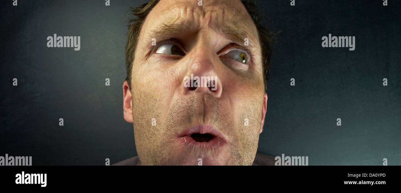 The head of a scared Man hiding from someone. - Stock Image