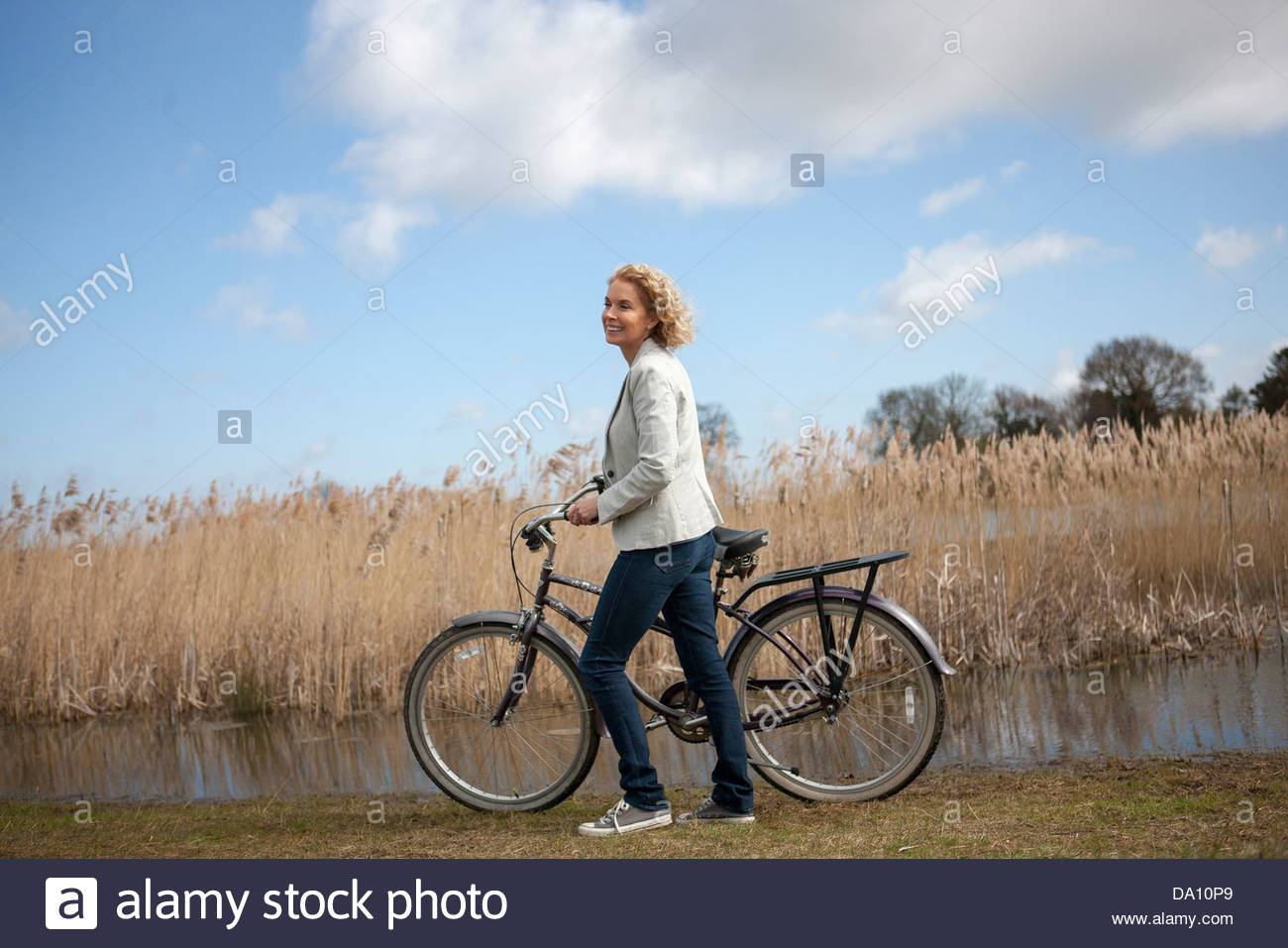 A mature woman pushing a bicycle next to a lake - Stock Image