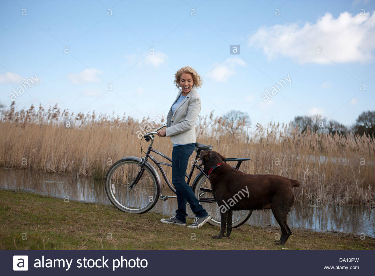 A mature woman pushing a bicycle next to a lake with her dog - Stock Image