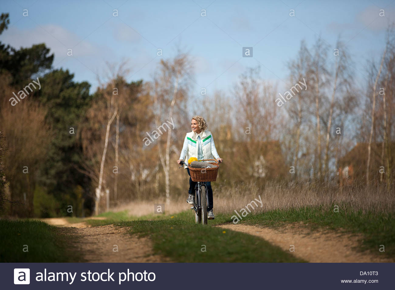 A mature woman cycling along a country path - Stock Image