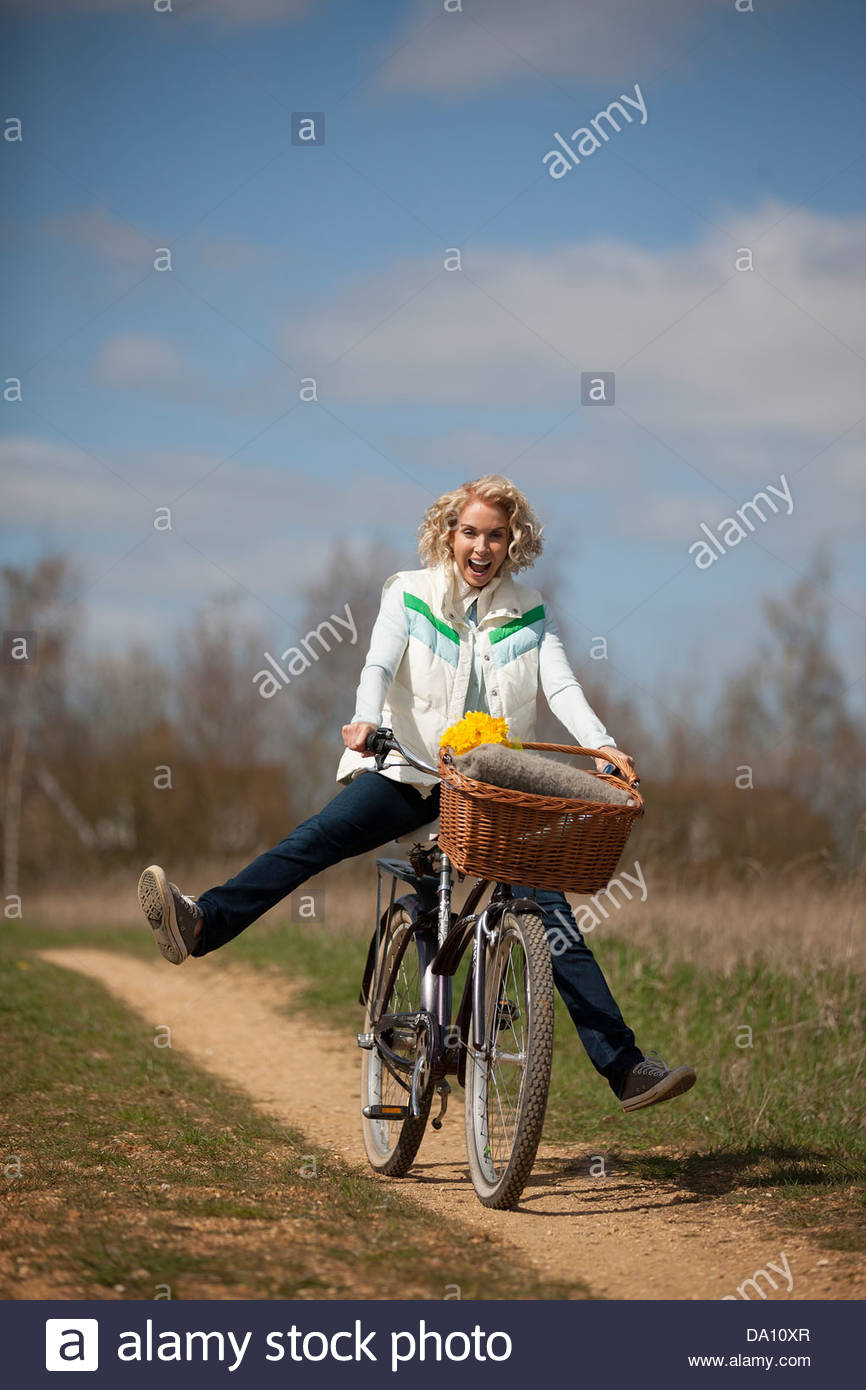 A mature woman cycling along a country path, legs outstretched - Stock Image
