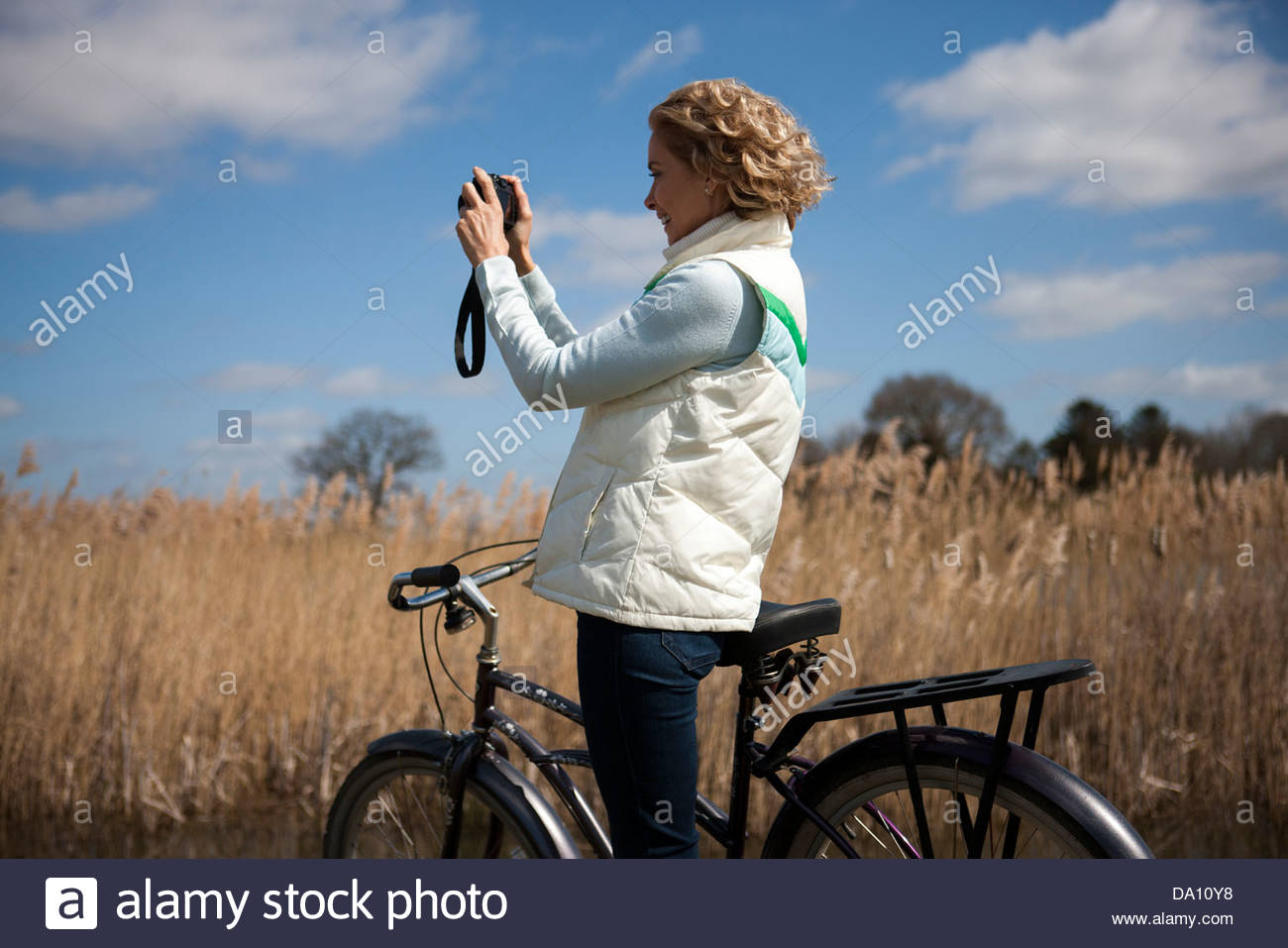 A mature woman taking a photograph whilst out cycling - Stock Image