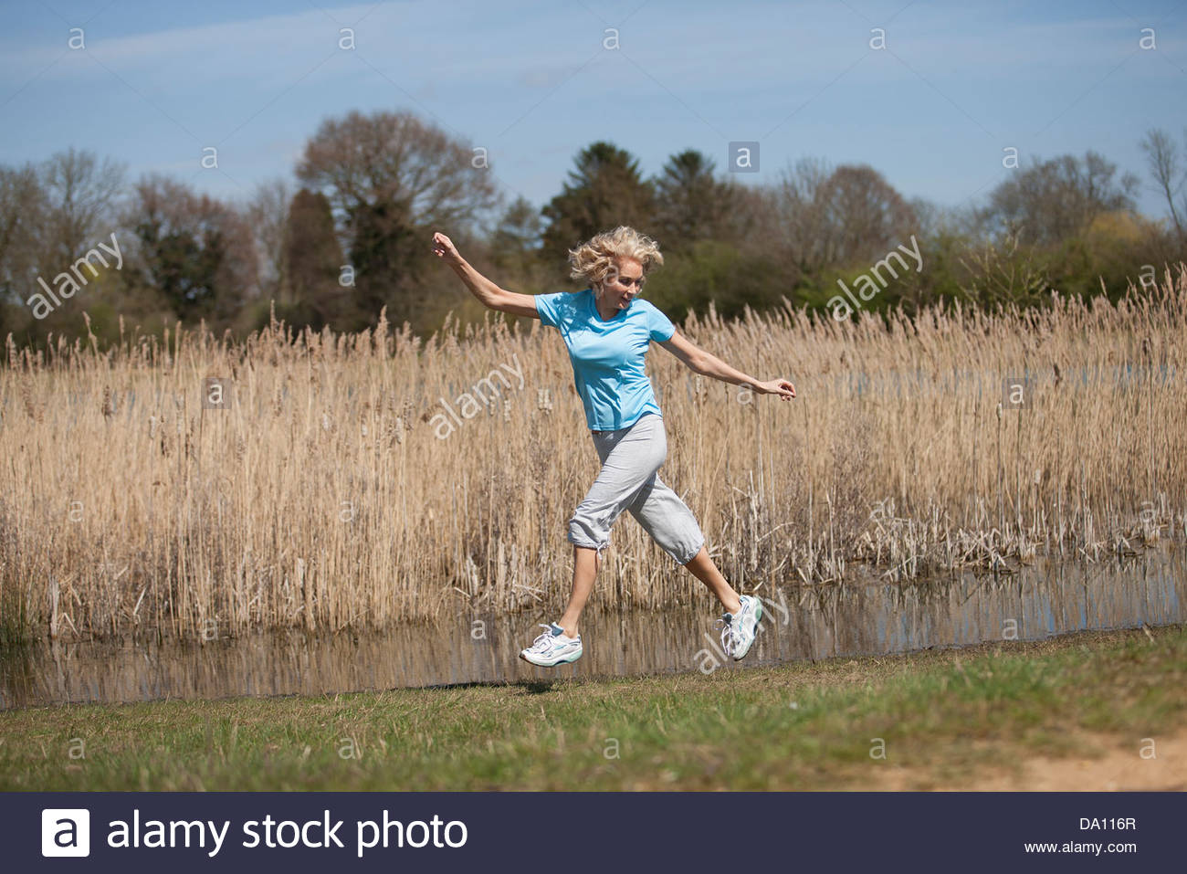 A mature woman running in the countryside, jumping with arms outstretched - Stock Image