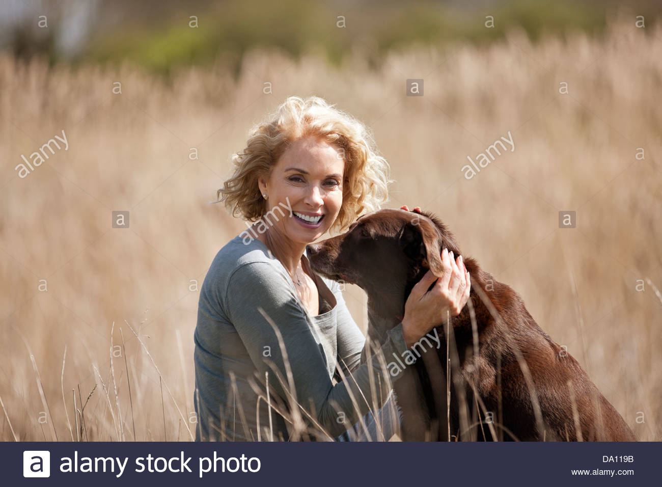 A mature woman sitting on the grass stroking her dog, smiling Stock Photo