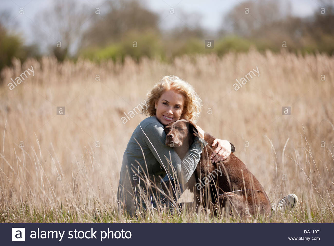 A mature woman sitting on the grass hugging her dog - Stock Image