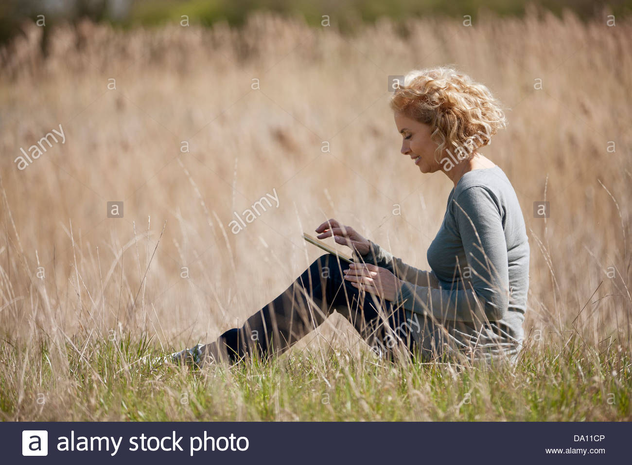 A mature woman sitting in long grass, using a digital tablet - Stock Image