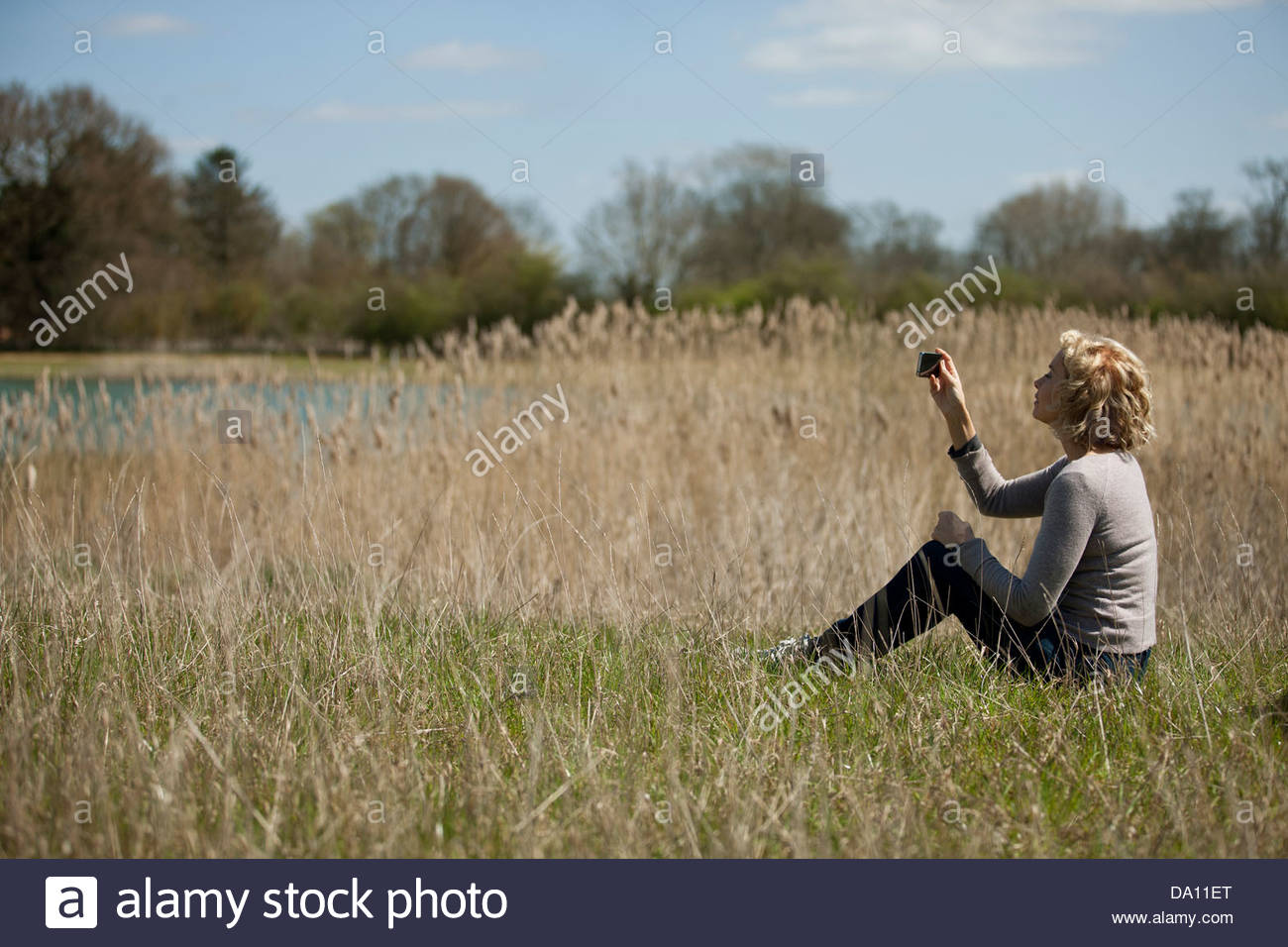 A mature woman sitting in long grass, taking a photo with a smartphone - Stock Image